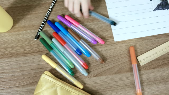 Felt pens, paper, ruler on table and boy's hands close-up. Camera move from left to right, top view. video