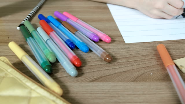 Felt pens, paper, ruler on table and drawing boy's hands close-up. Camera move from left to right. video