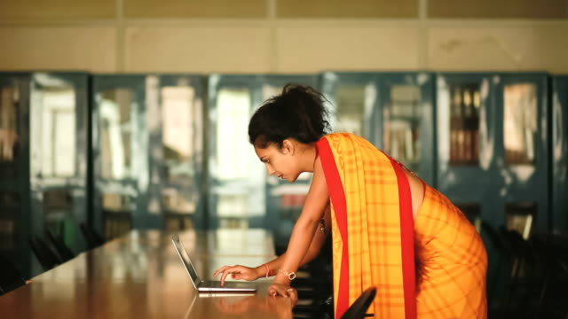 Female Academician in Library Lady professor using laptop in a college library. indian subcontinent ethnicity stock videos & royalty-free footage