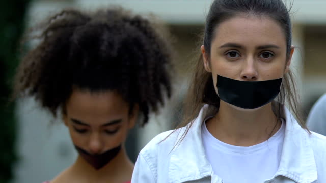 Female activists demonstrating with taped mouth, march against domestic violence