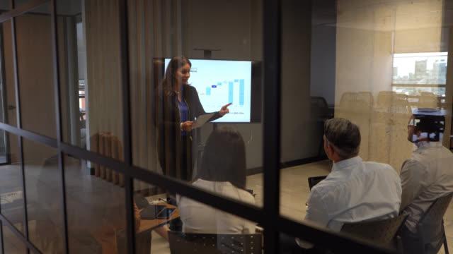 stockvideo's en b-roll-footage met vrouwelijke volwassen manager die haar team aanpakt met behulp van een visuele hulpmiddel tijdens een zakelijke bijeenkomst op kantoor - marketing planning