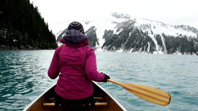 female adventurer canoeing an alpine lake - canada travel stock videos and b-roll footage