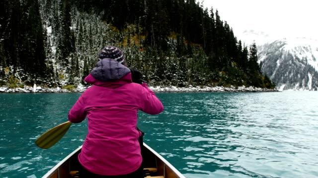 Female adventurer canoeing an alpine lake video