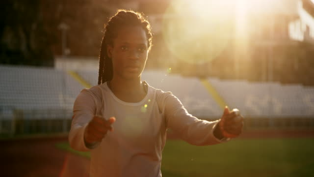 SLO MO Female African-American athlete stretching in the stadium at sunset video