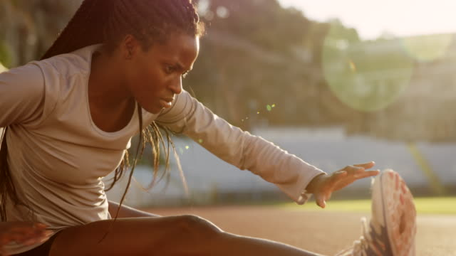SLO MO Female African-American athlete stretching in the stadium in setting sun video