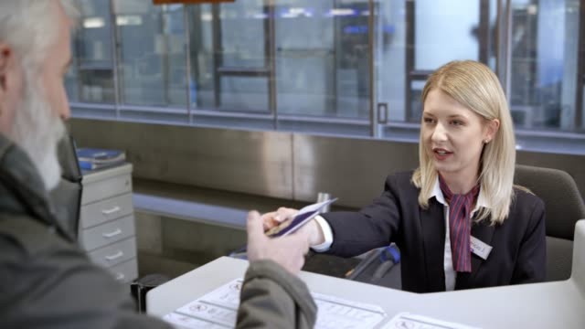 Female airline employee at the check in desk handing passport to the passenger after putting a tag on the luggage video