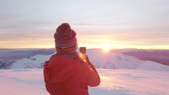 Female alpine climber is shooting photos with her cellphone in the peak of high altitude mountain in winter
