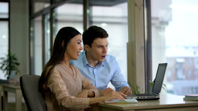 female and male co-workers reading email on laptop and becoming extremely happy - collega d'ufficio video stock e b–roll