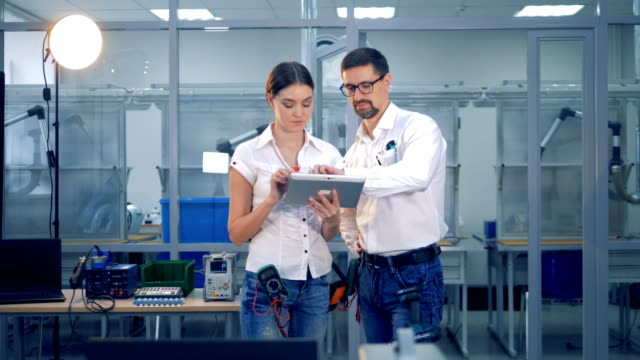 Female and male engineers are discussing something with a tablet computer video