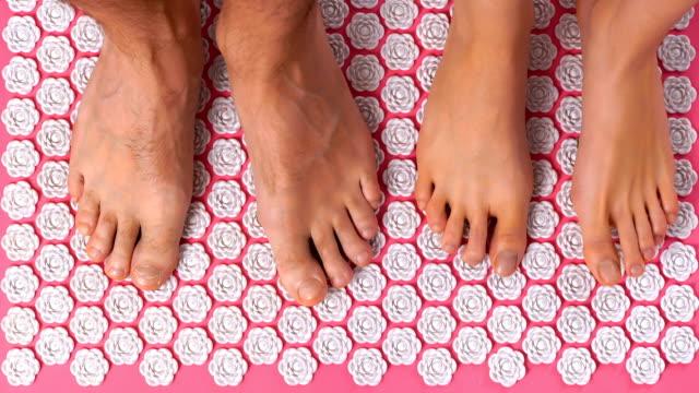 kvinnliga och manliga fötter trampa försiktigt på akupunktur massage matta. topp-vy - acupuncture bildbanksvideor och videomaterial från bakom kulisserna
