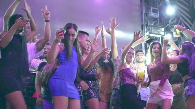 weibliche und männliche freunde tanzen in der disco mit getränken - lateinische schrift stock-videos und b-roll-filmmaterial