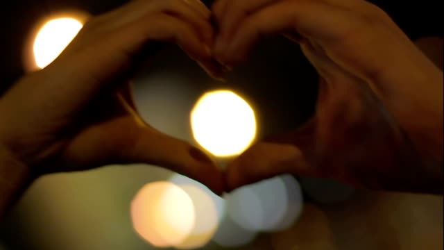 Female and male hands showing heart hand sigh, love and tenderness, relationship video