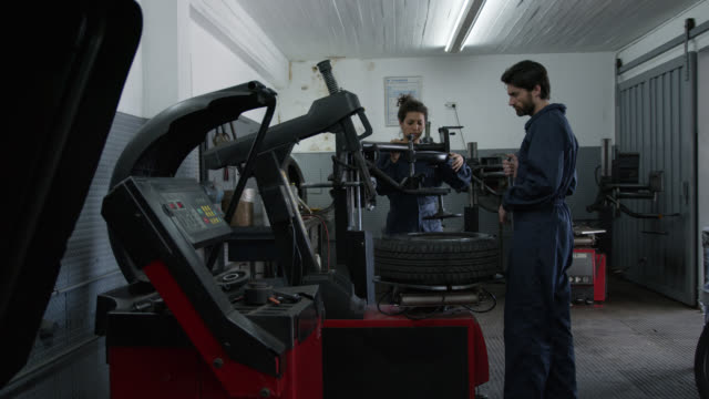 Female and male mechanics fixing punctured tires at a garage