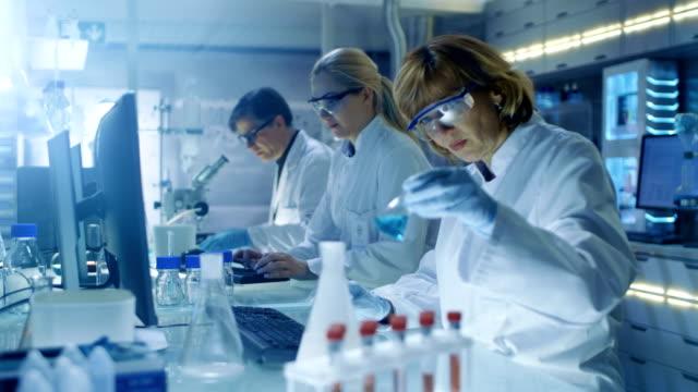 Hembra y macho los científicos trabajando en sus computadoras en grande moderno laboratorio. Varios estantes con vasos, productos químicos y diverso equipo técnico es Visible. - vídeo