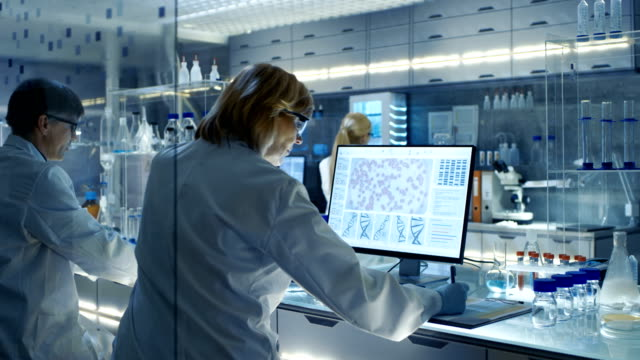 Female and Male Scientists Working on their Computers In Big Modern Laboratory. Various Shelves with Beakers, Chemicals and Different Technical Equipment is Visible. video