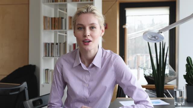 女性応募者は、ビデオ会議で就職の面接を通過するカメラを見ます - 合意点の映像素材/bロール