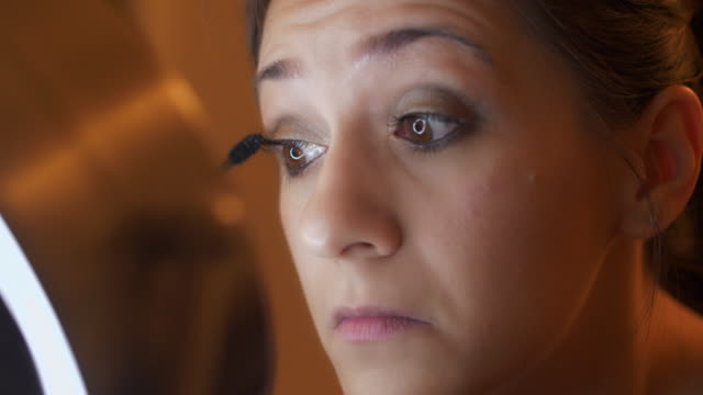 female applying mascara to right eyelashes move right - lunghezza video stock e b–roll