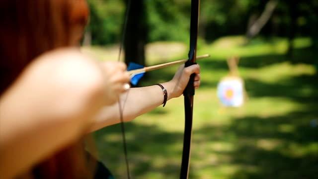 vidéos et rushes de archer féminin dans le fieald - tir à l'arc