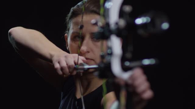 vidéos et rushes de archer féminin tir arc sur fond noir - tir à l'arc