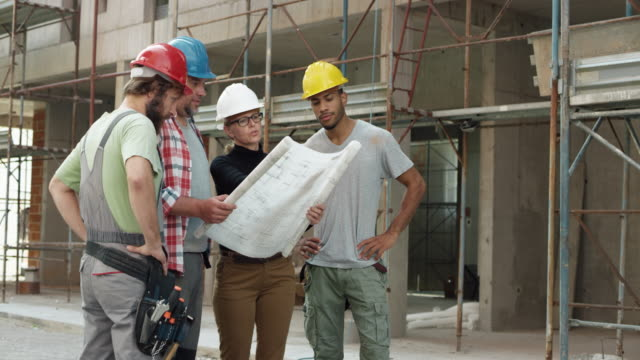 Female architect, a foreman and two construction workers looking at the plan outside at the construction site and pointing at the building to check the progress video