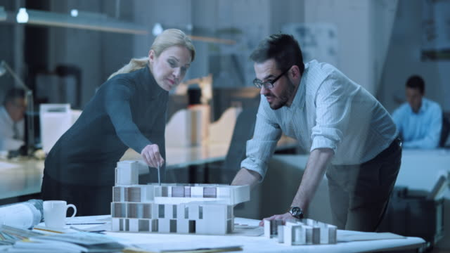 DS Female architect and colleague constructing an architectural model video