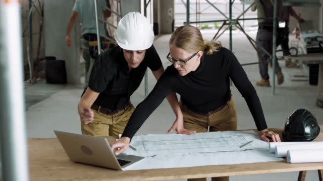 female architect and female construction coordinator checking the plans at the construction site - industria edile video stock e b–roll