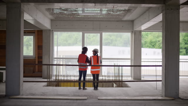 ld female architect and forewoman talking while looking at the concrete structures at the construction site - spranga video stock e b–roll