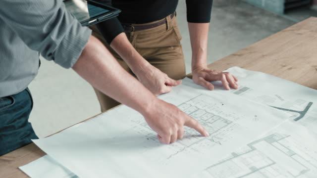 여성 건축가 및 건설 현장에서 디지털 태블릿에 그 테이블에 대 한 계획을 비교 하는 남성 엔지니어 - 검사 보기 스톡 비디오 및 b-롤 화면