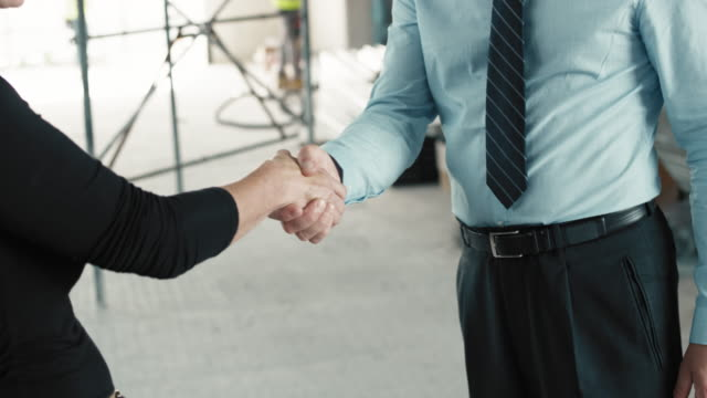 Female architect and male project manager shaking hands at the construction site video