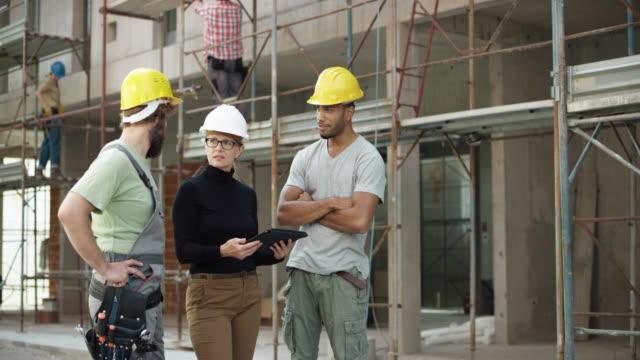 vídeos de stock, filmes e b-roll de arquiteto feminino e dois trabalhadores da construção verificando o plano sobre o tablet digital exterior e apontando para o edifício, para verificar o progresso - camiseta preta