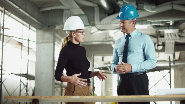 DS Female architect discussing the plans on site with the male project manager video