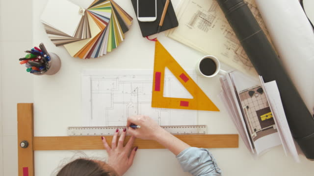 Female architect drawing on blueprint using rulers Female architect drawing on blueprint using rulers. Top view of table with architects plan. interior designer stock videos & royalty-free footage
