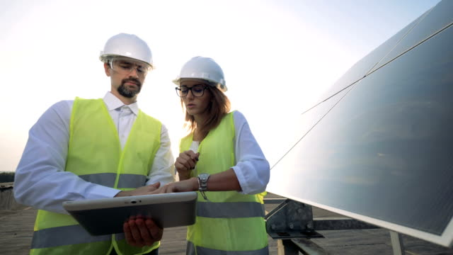 Female architect, engineer talking with male engineer near solar battery. Alternative energy concept