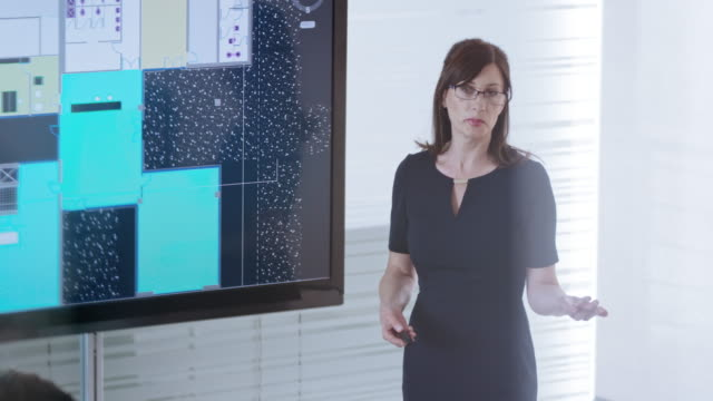 female architect explaining plan details shown on large screen in the conference room - leanincollection stock videos & royalty-free footage