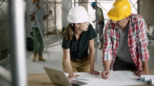 Female architect explaining the foreman details of the plan by checking on the laptop and showing him on the plan sheet video
