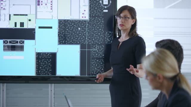 female architect giving a presentation of the plans for the project using the screen in the meeting room - leanincollection stock videos & royalty-free footage