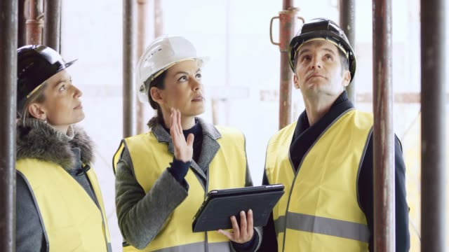 female architect holding a tablet and explaining details of the construction plan to the male and female investor - industria edile video stock e b–roll