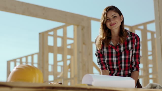 Female architect on construction site looking at blueprints video