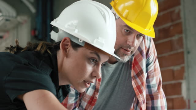 female architect showing a foreman details on the laptop at the construction site - leanincollection stock videos & royalty-free footage