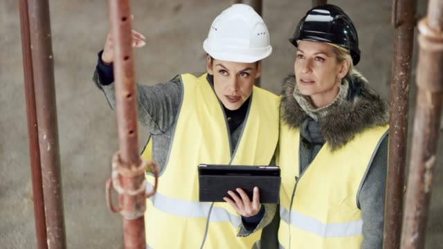 female architect showing the female investor how a detail from the plan will be implemented into the building - fianco a fianco video stock e b–roll