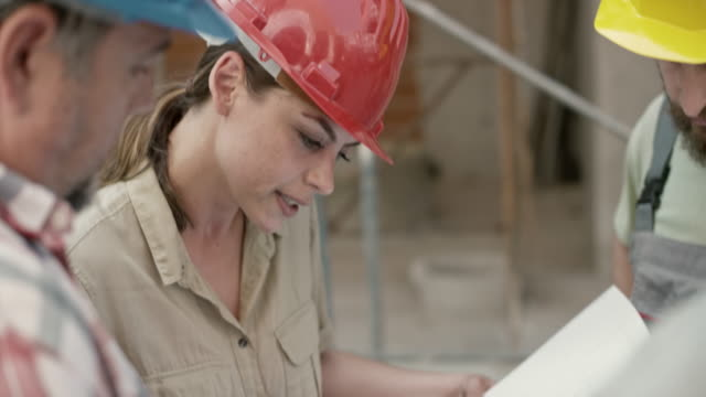 female architect talking to the construction workers and pointing out details on the plan she is holding - leanincollection stock videos & royalty-free footage