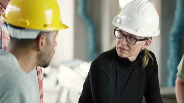 female architect talking to workers at the construction site, discussing the plans set on the table - leanincollection stock videos & royalty-free footage