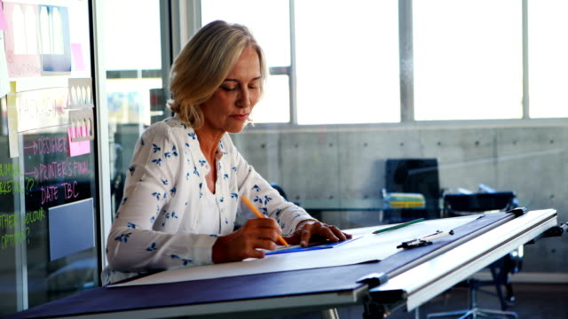 Female architect working on blueprint over drafting table 4k video