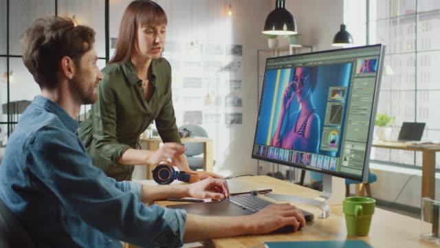 la direttrice artistica femminile consulta la collega designer, lavorano su un ritratto nel software di fotoritocco. lavorano in un loft dell'ufficio fresco. sembrano molto creativi e cool. - fotografia immagine video stock e b–roll