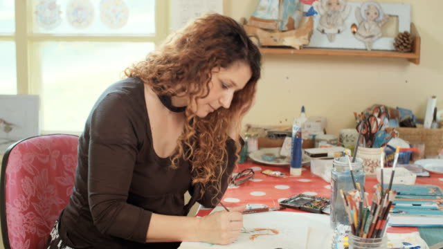 Female artist in her studio painting with water colors and pencils video