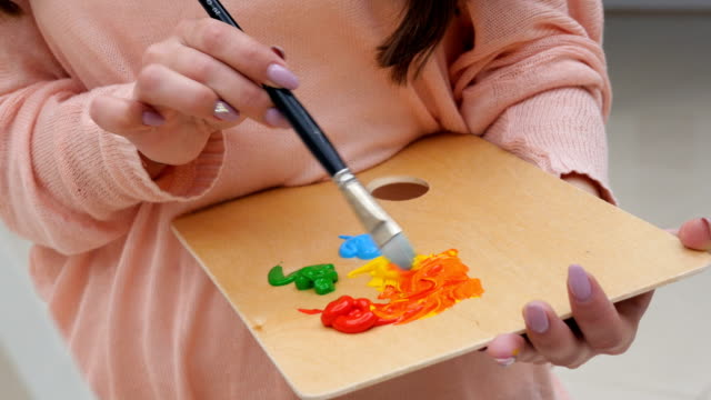Female artist mixing colors close up. video
