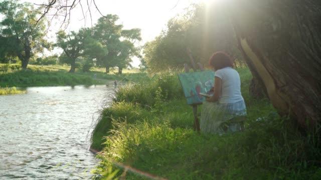 vidéos et rushes de peinture d'artiste femelle à l'extérieur - toile à peindre