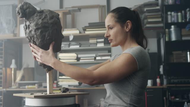 Female artist sculpting face video