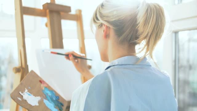 vídeos y material grabado en eventos de stock de artista femenina empezando a pintar en el caballete, disfrutando de la afición favorita - espalda humana