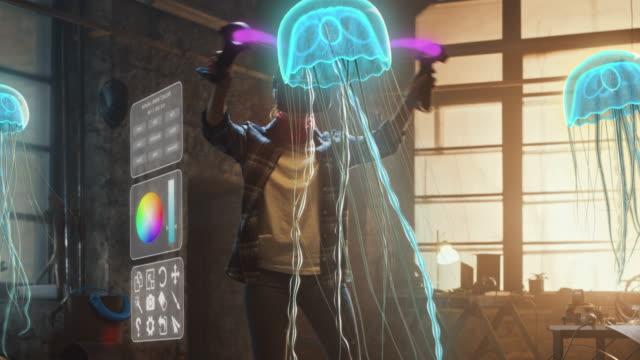 vídeos y material grabado en eventos de stock de artista femenina que usa auriculares de realidad aumentada que trabajan en la escultura abstracta de medusas de medusas 3d con joysticks, utiliza gestos para crear un concepto multimedia de internet de alta tecnología art.3d animación efecto especial - organismo vivo